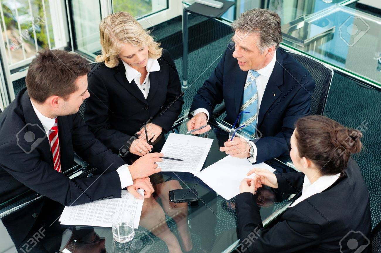 Business - meeting in an office; the businesspeople are discussing a document Stock Photo - 9860947