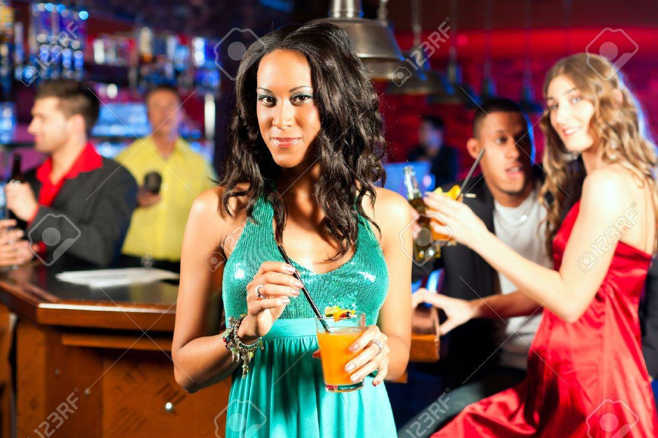Group of party people with cocktails in a bar or club having fun; one woman is looking into the camera Stock Photo - 9860553
