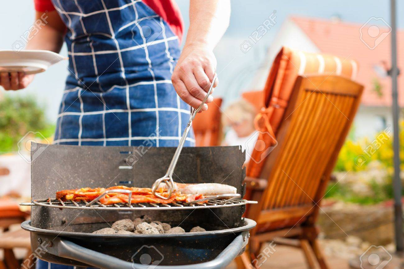 Happy family having a barbecue in summer; father stands next to the fire Stock Photo - 9860807