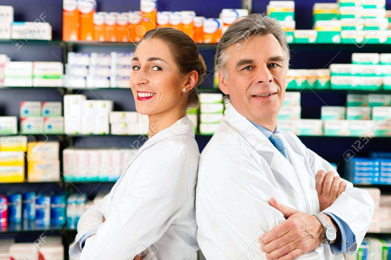 two pharmacists standing in pharmacy or drugstore in front of stock photo two pharmacists standing in pharmacy or drugstore in front of shelves pharmaceuticals