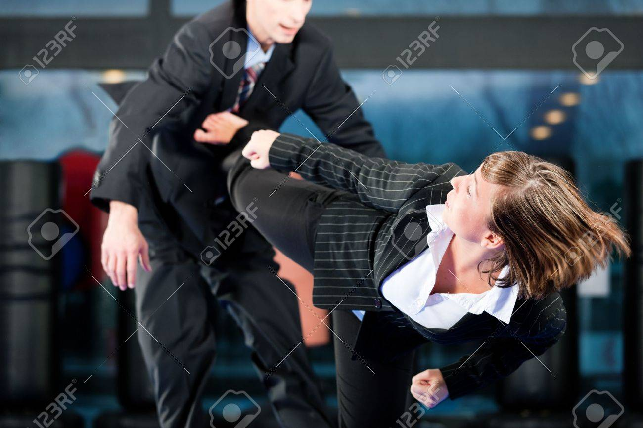 Business concept - People in a gym in martial arts training exercising Taekwondo, both wearing suits Stock Photo - 10016587