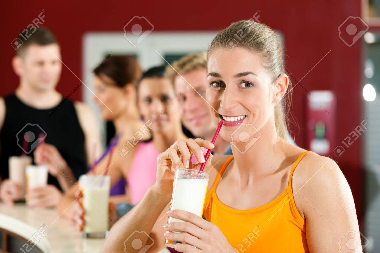 People drinking protein shake after workout in gym or fitness club Stock Photo - 10021151