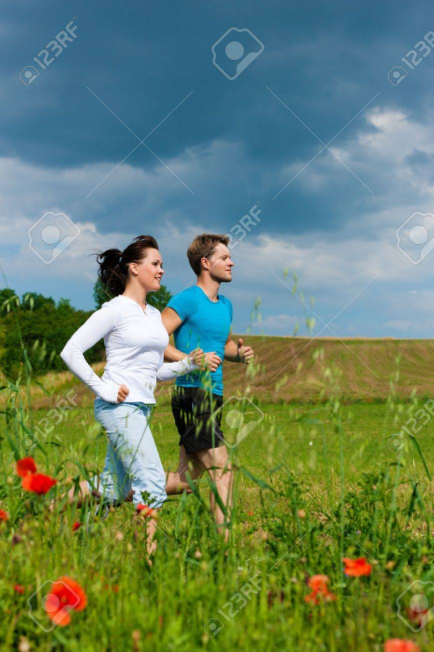Young fitness couple doing sports outdoors; jogging on a green meadow in summer under the sky with lots of clouds Stock Photo - 10021053