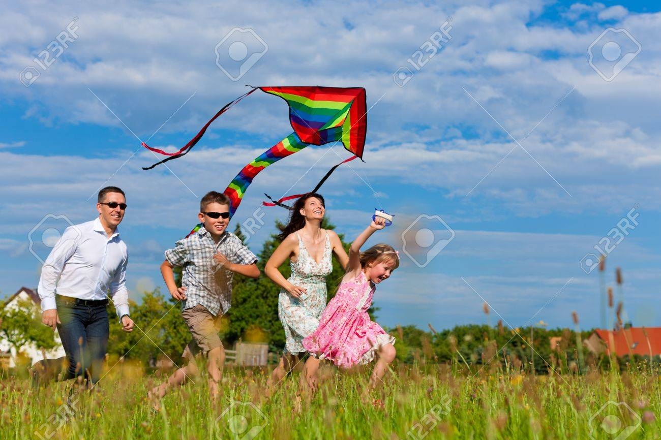 Happy family - mother, father, children - running over a green meadow in summer; they fly a kite Stock Photo - 10021159