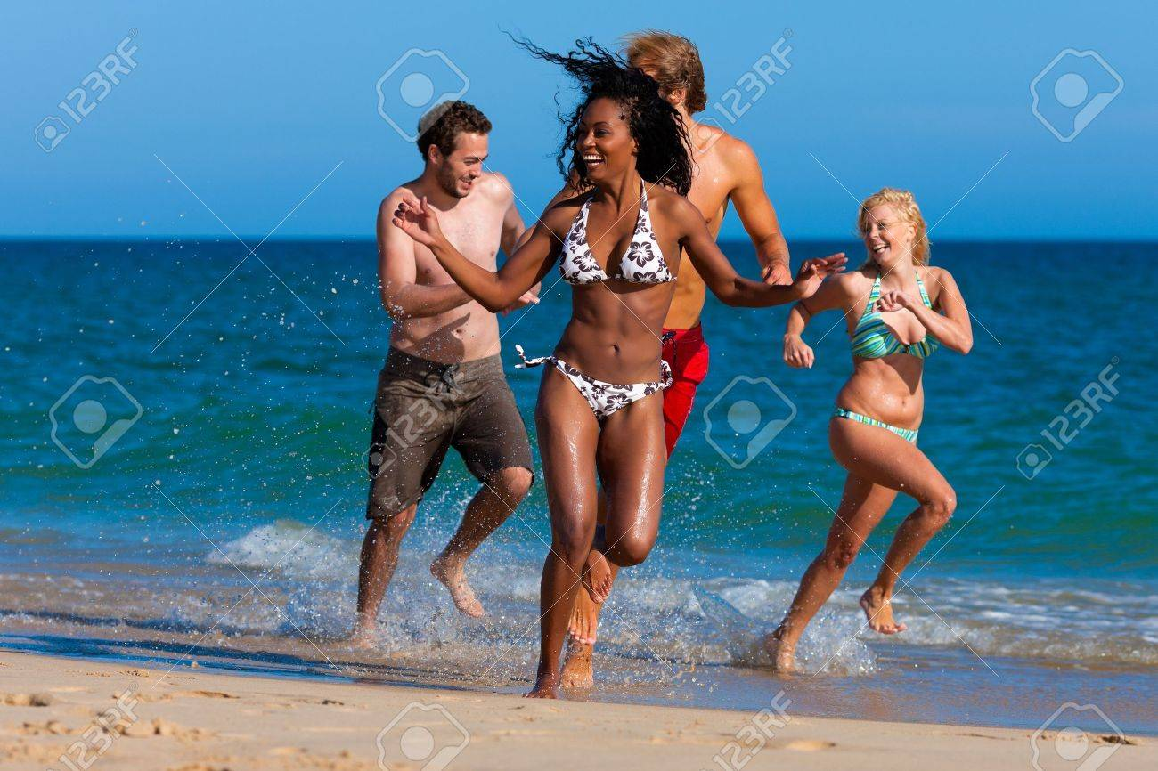 Four friends - men and women - on the beach having lots of fun in their vacation running through the water Stock Photo - 10050453