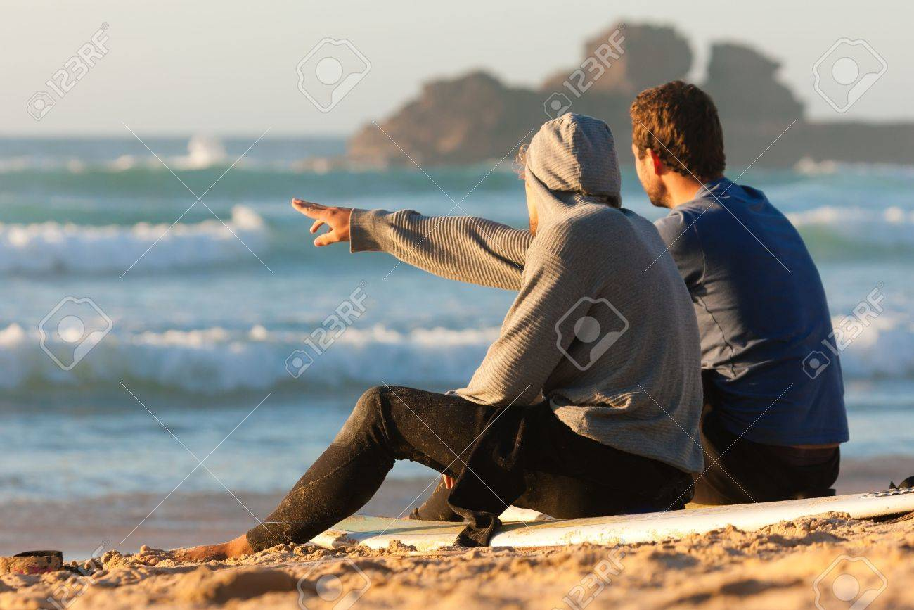 10021186-Two-surfers-sitting-on-their-surf-boards-on-the-beach-discussing-the-waves-Stock-Photo.jpg
