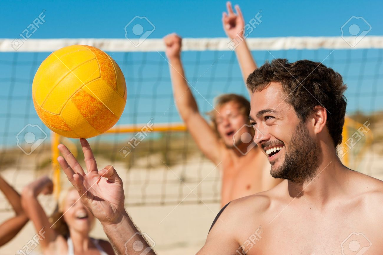 Group of friends - women and men - playing beach volleyball, one in front doing tricks to the ball Stock Photo - 10021871