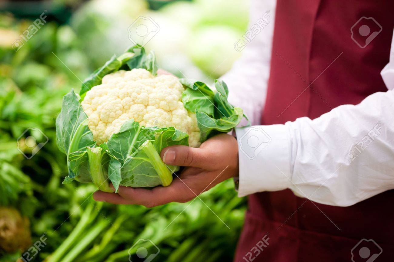 Man – only hands to be seen - in supermarket as shop assistant; he is carrying a cauliflower Stock Photo - 10040889