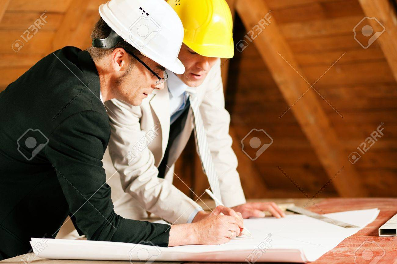 Architect and construction engineer or surveyor discussion plans and blueprints. Both are wearing hardhats and are standing on the construction site of a home indoors Stock Photo - 10041160