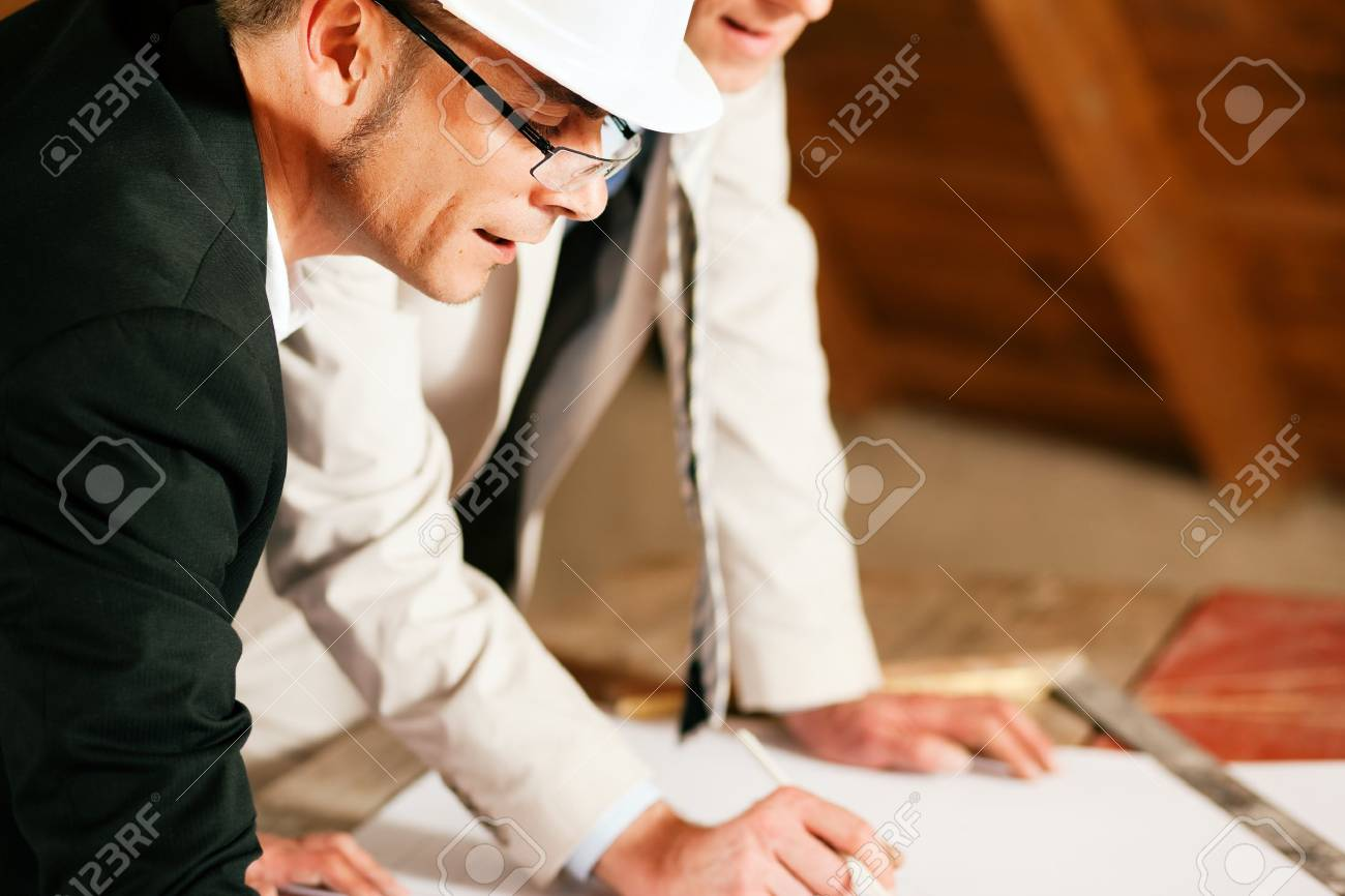 Architect and construction engineer or surveyor discussion plans and blueprints. Both are wearing hardhats and are standing on the construction site of a home indoors Stock Photo - 10041157
