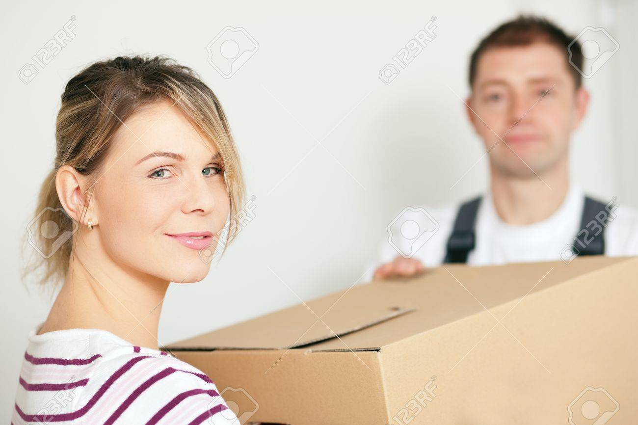 Woman moving in her new house, she is getting friendly help by a mover who is carrying the boxes Stock Photo - 10091456