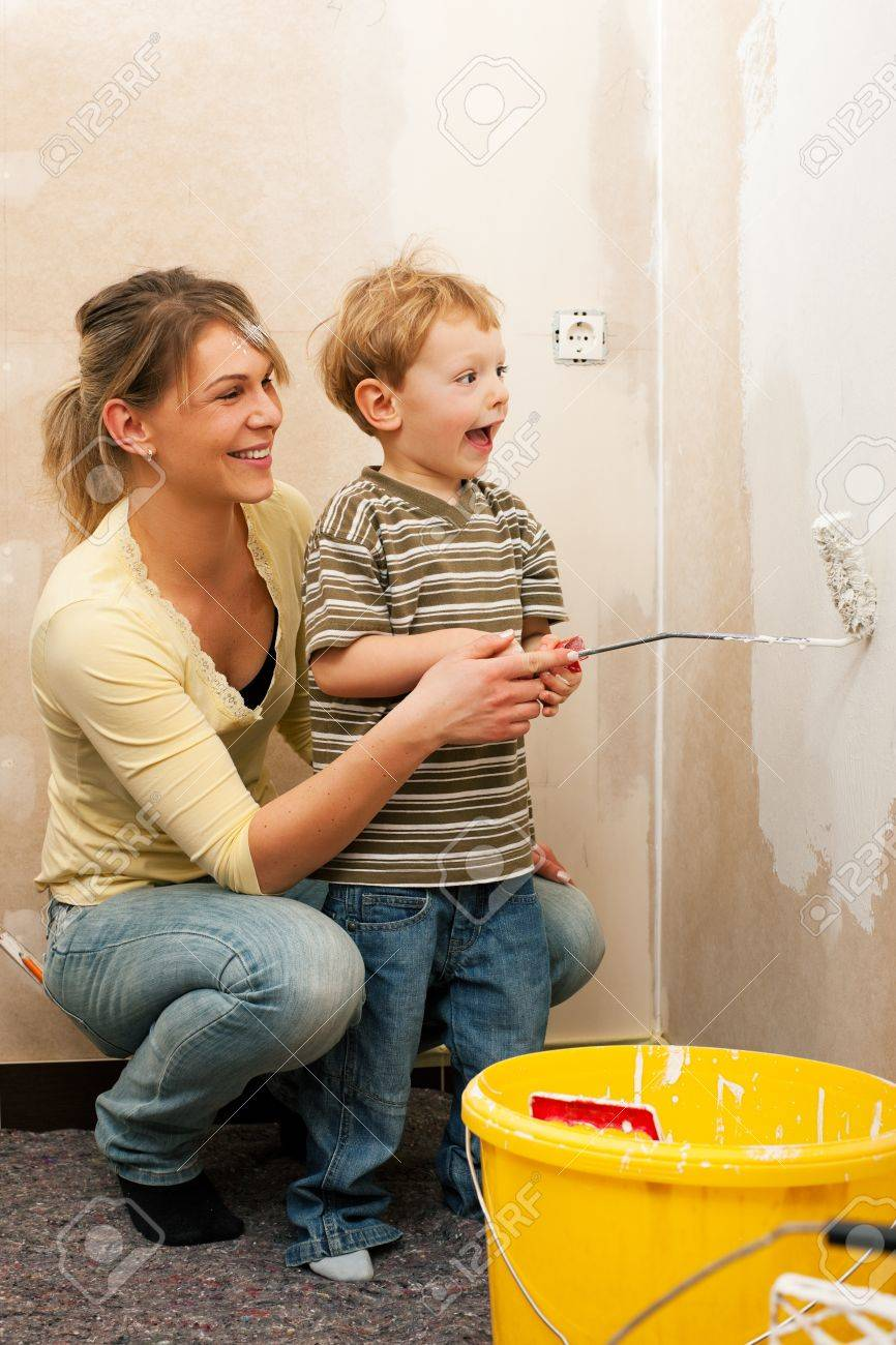 Family - mother with son - painting the wall of their new home or apartment, apparently they just moved in Stock Photo - 10091502