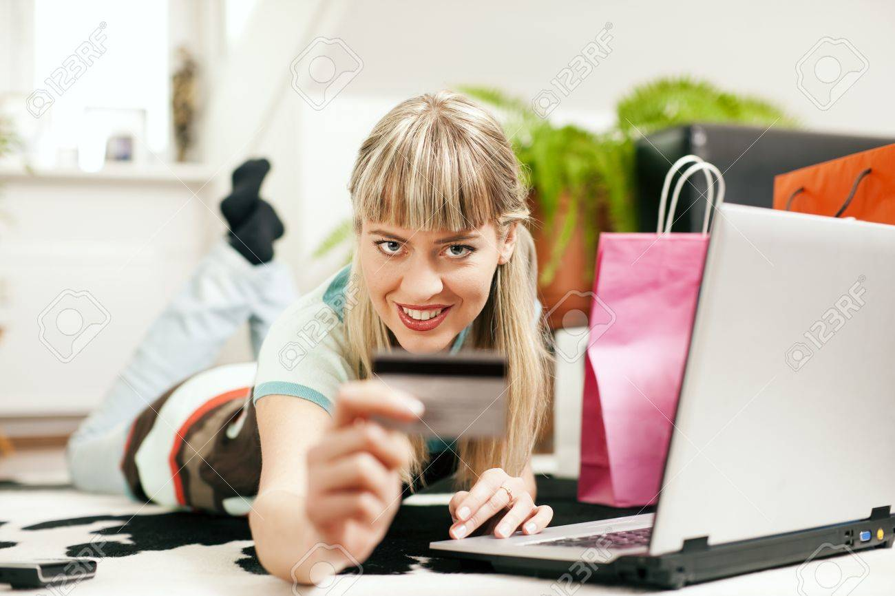 Woman lying in her home living room on floor shopping or doing banking transactions online in the Internet, emphasized by shopping bags in the background and her holding a credit card Stock Photo - 10256918