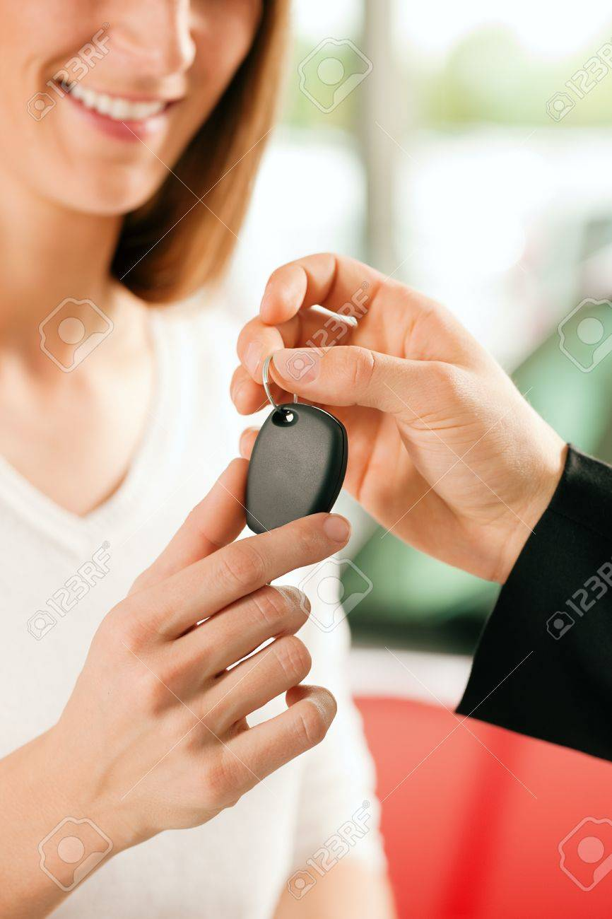 Woman at a car dealership buying an auto, the sales rep giving her the key, macro shot with focus on hands and key Stock Photo - 10260913