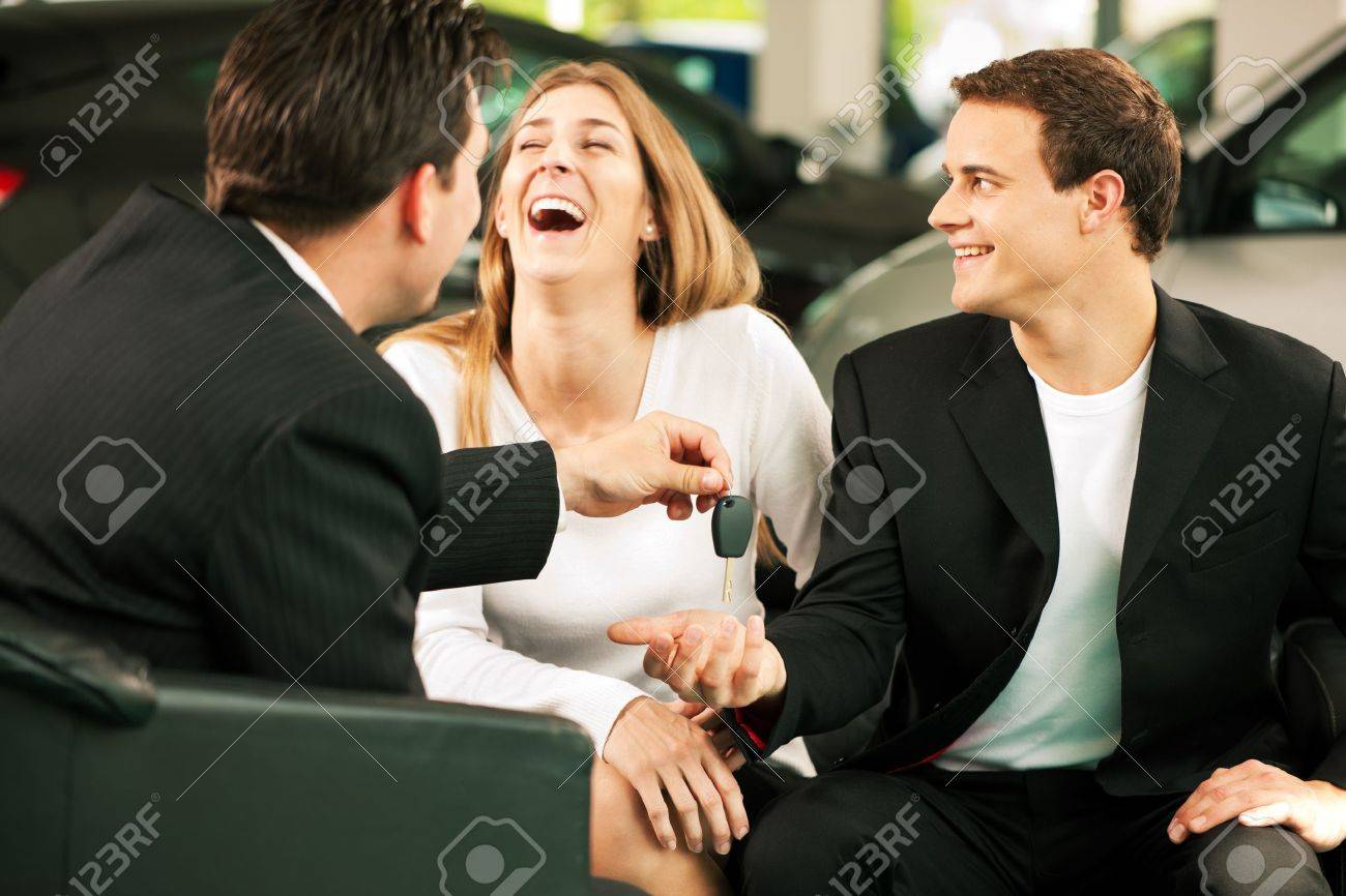 Sales situation in a car dealership, the young couple is signing the sales contract to get the new car in the background Stock Photo - 10260949