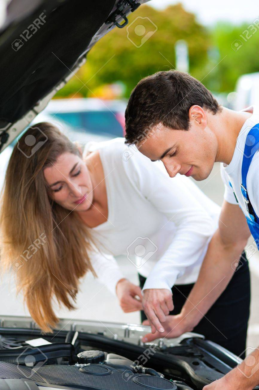 Woman talking to a car mechanic in a parking area, both are standing next to the car Stock Photo - 10260982