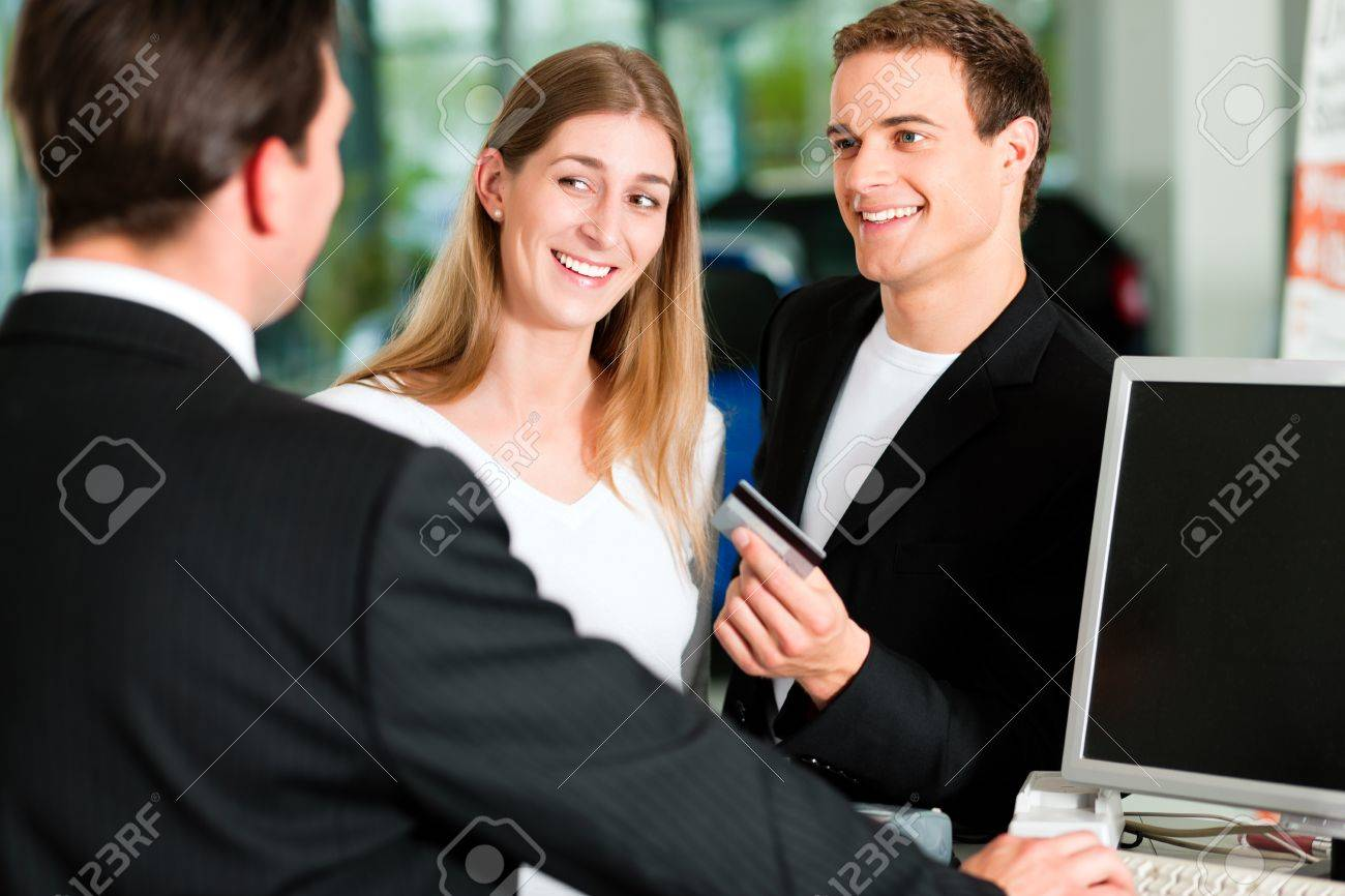 Sales situation in a car dealership, the young couple is giving the credit card to pay for the new car Stock Photo - 10260953