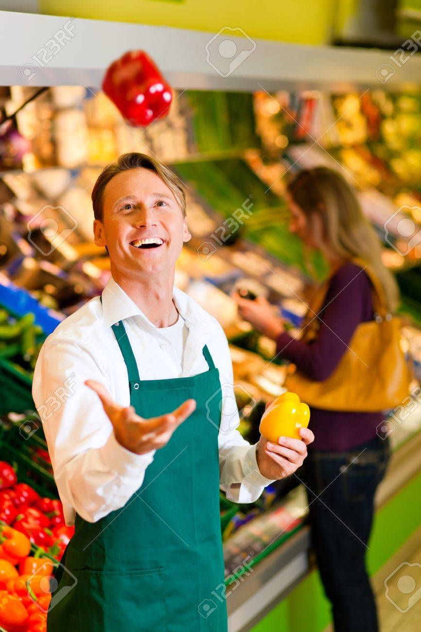Shop assistant in a supermarket at the vegetable shelf; he is tossing a bell pepper Stock Photo - 10260950