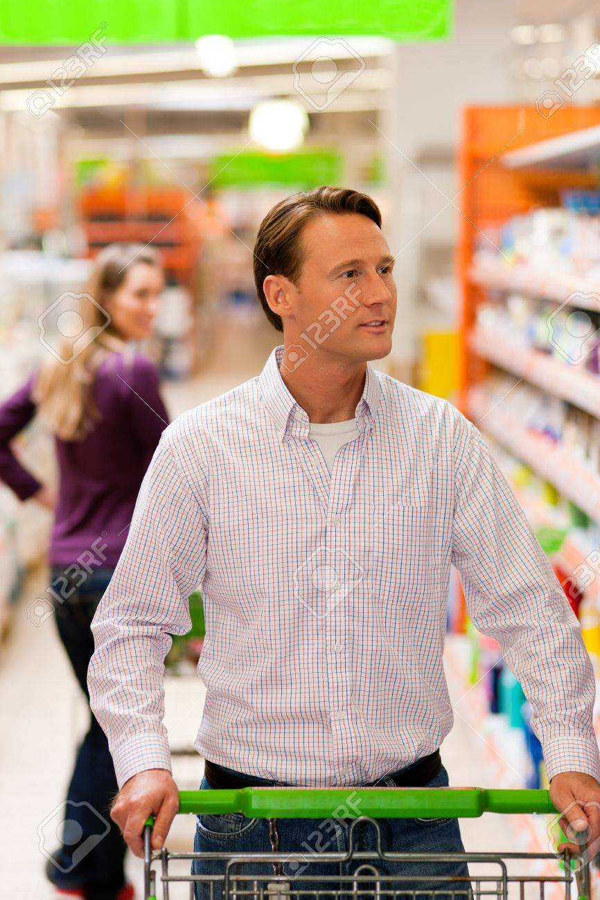 Woman in the supermarket looking after a guy she just met shopping there, she is ready to flirt a bit Stock Photo - 10260917