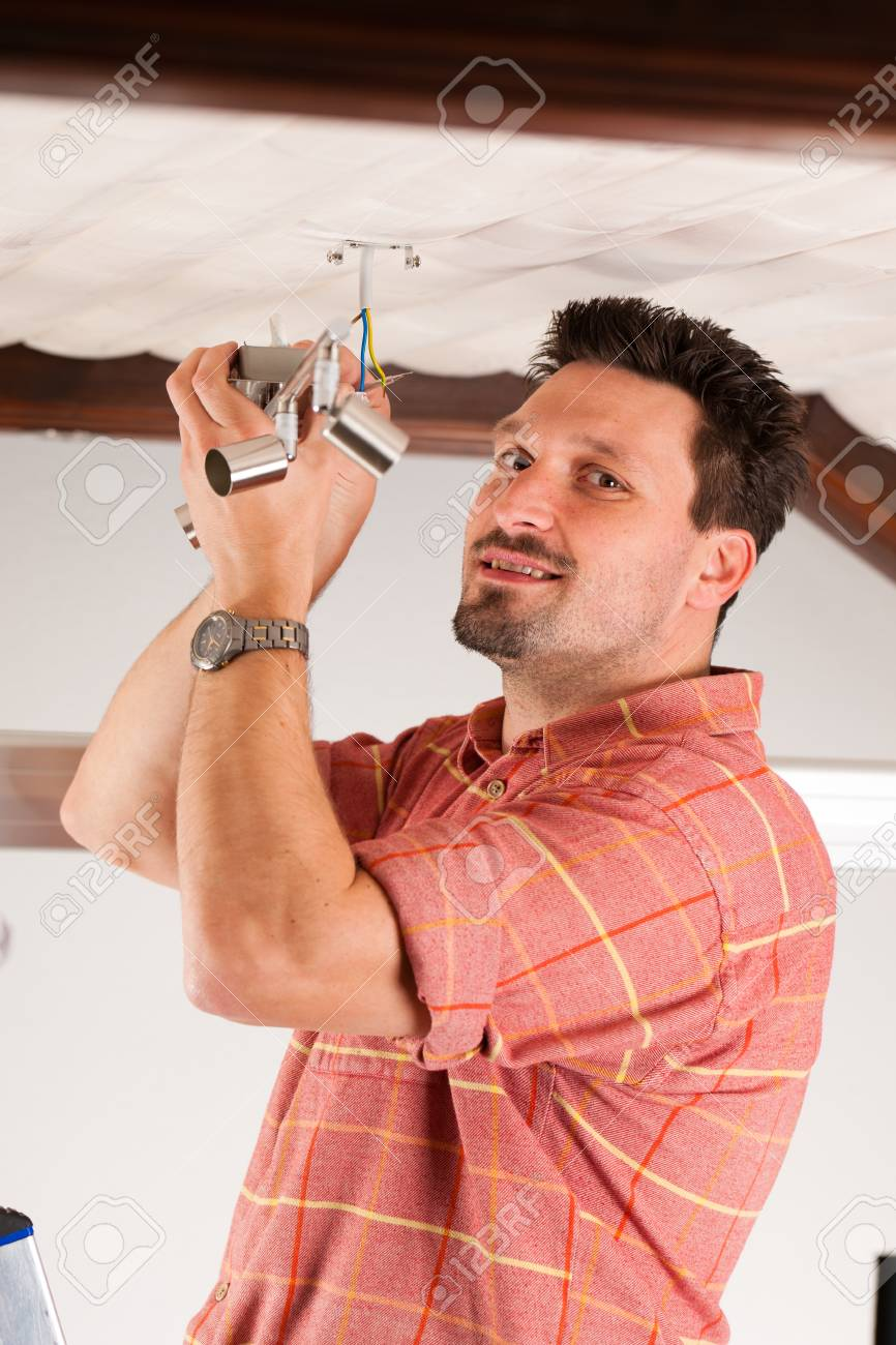 Worker is installing a luster in a Haus on the ceiling Stock Photo - 10269955