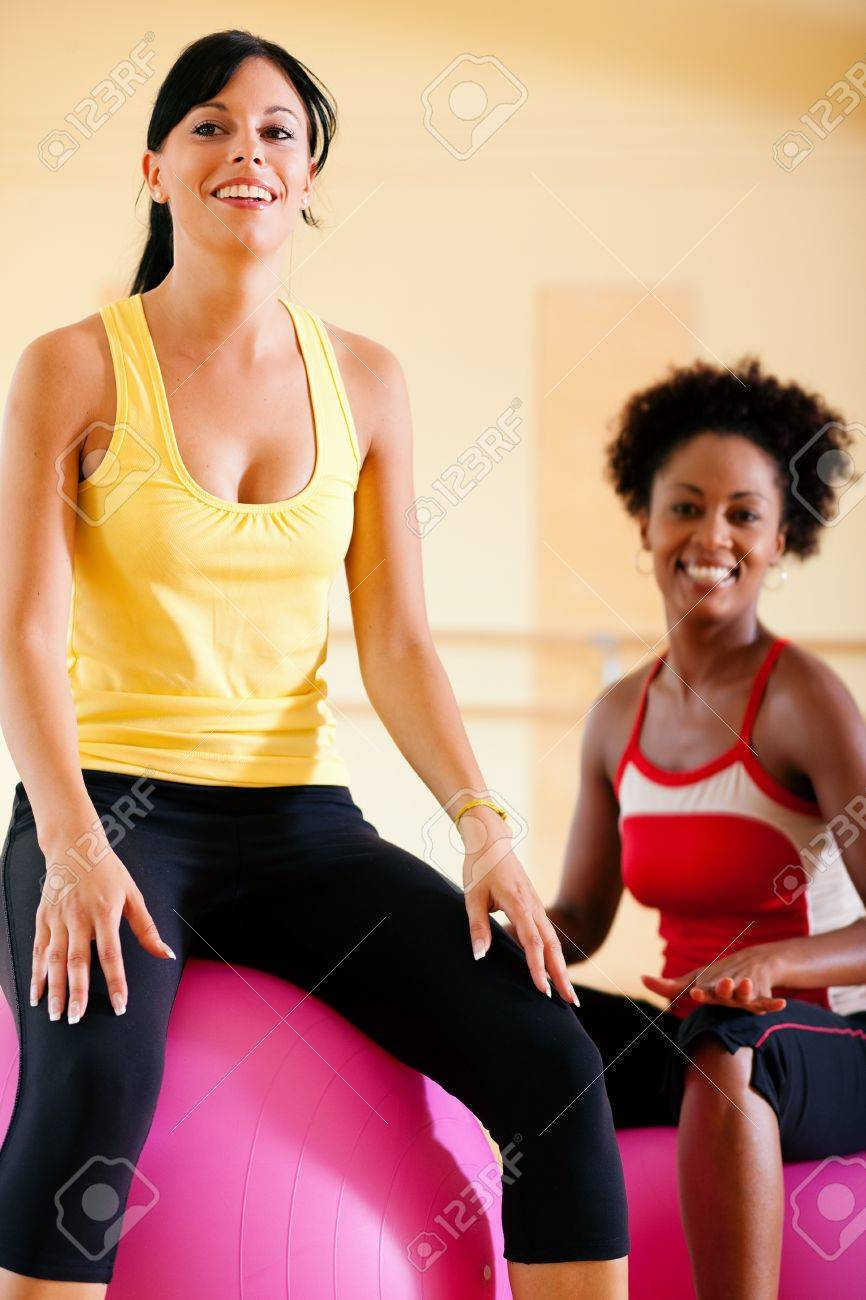 Two young, healthy women doing gymnastics exercises with a fitness ball in gym Stock Photo - 10305949