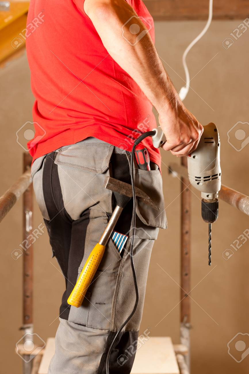 construction worker with hand drill standing on a scaffold Stock Photo - 10330283