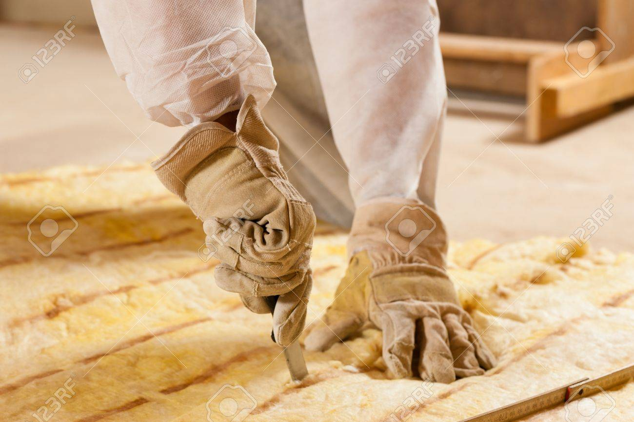 Man - only hand to be seen - cutting some glass wool as material for thermal insulation of a new building Stock Photo - 10330262