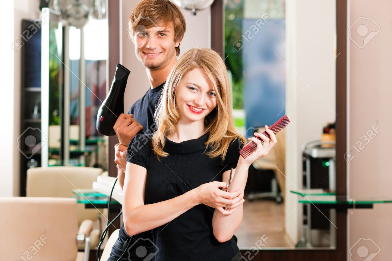 Two hairdresser - man and woman - posing for the camera in the hairdresser Stock Photo - 10428328