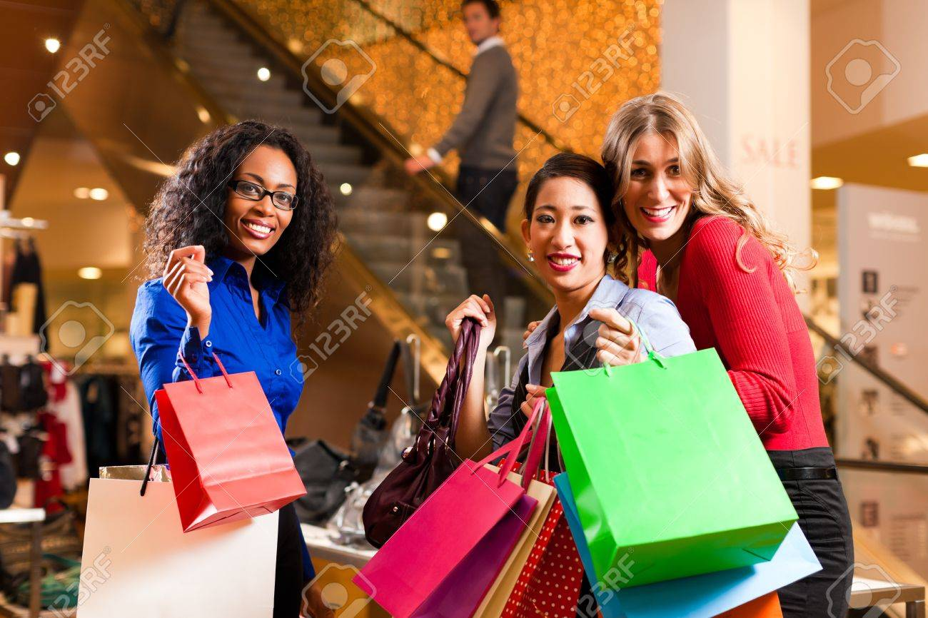 Group of three women - white, black and Asian – shopping downtown in a mall; in the background a man on escalator Stock Photo - 10428105