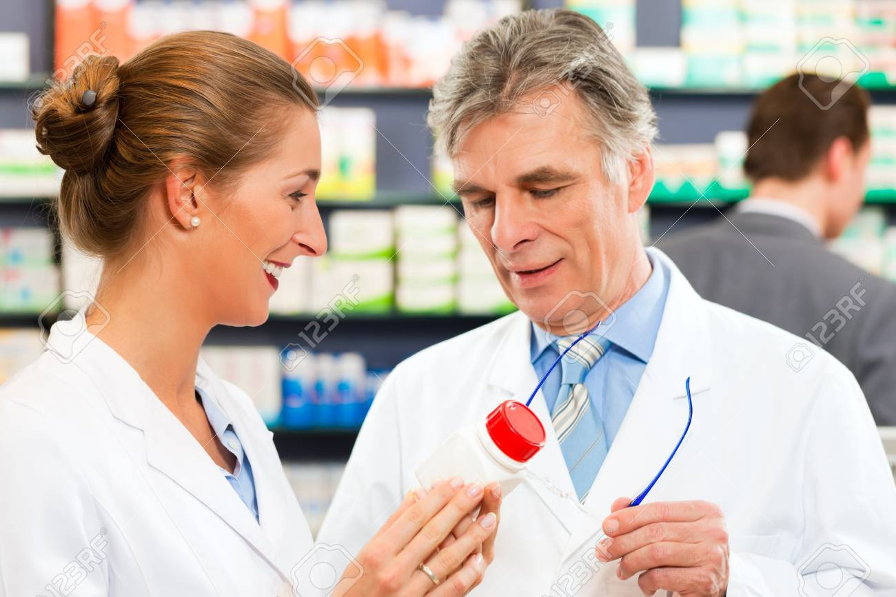 Two pharmacists in pharmacy consulting Stock Photo - 10427974
