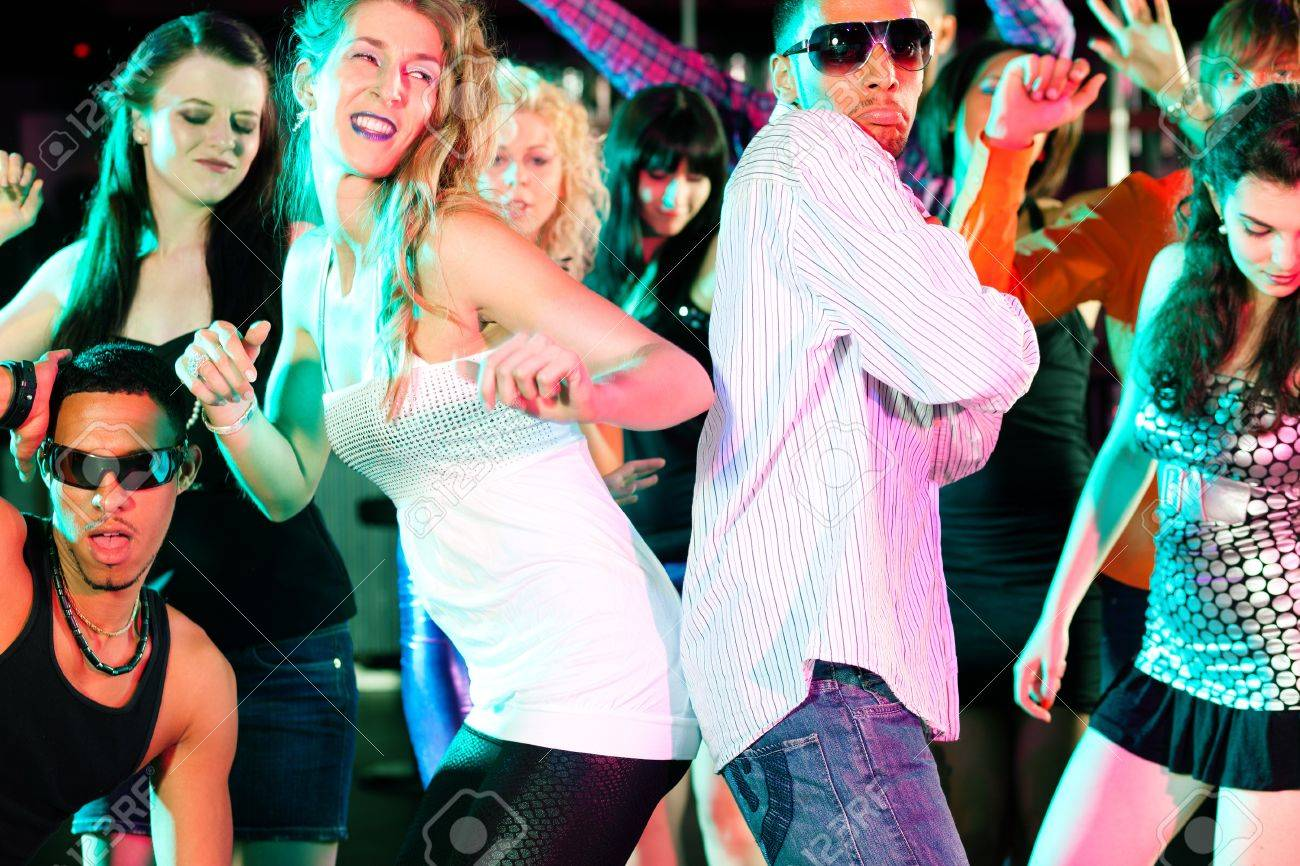 Group of friends - men and women of different ethnicity - having fun in a disco or nightclub Stock Photo - 10448839
