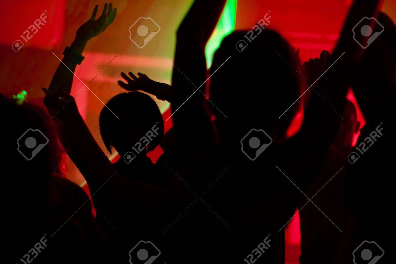 Silhouettes of dancing people having a celebration in a disco club, the light show is sending laser beams through the backlit scene Stock Photo - 10448758