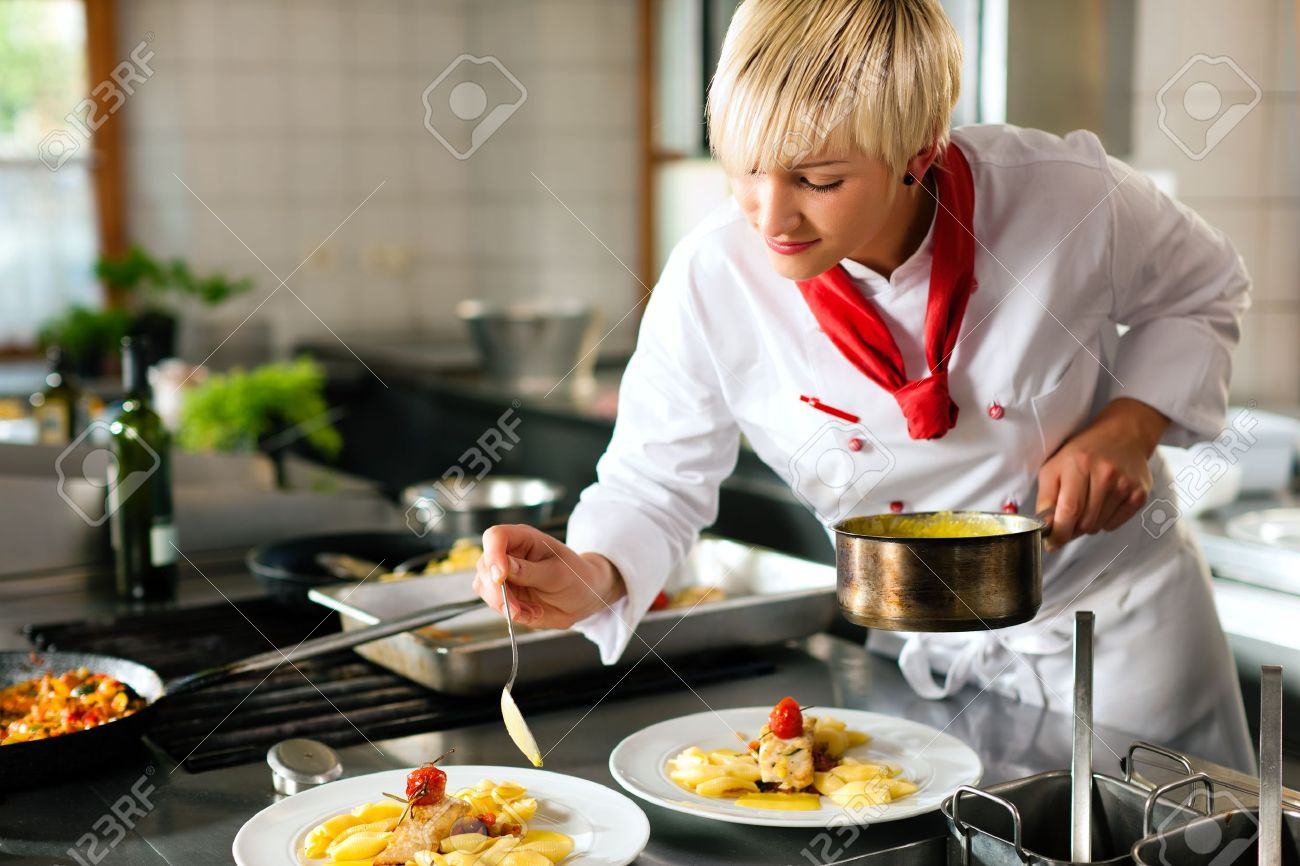 Female chef in a restaurant or hotel kitchen cooking delicious food she is decorating the