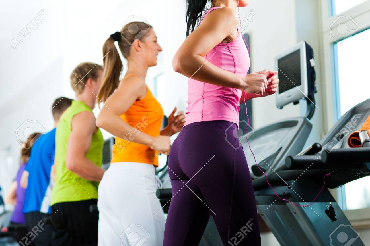 Running on treadmill in gym or fitness club - group of women and men exercising to gain more fitness Stock Photo - 10448847