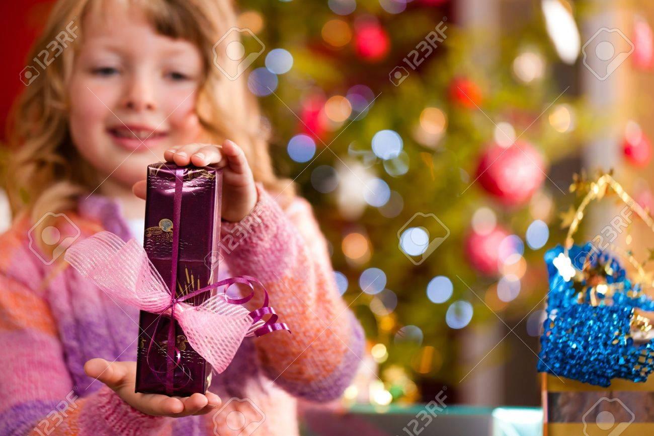 Christmas - happy little girl with Xmas present on Christmas Eve Stock Photo - 10718377