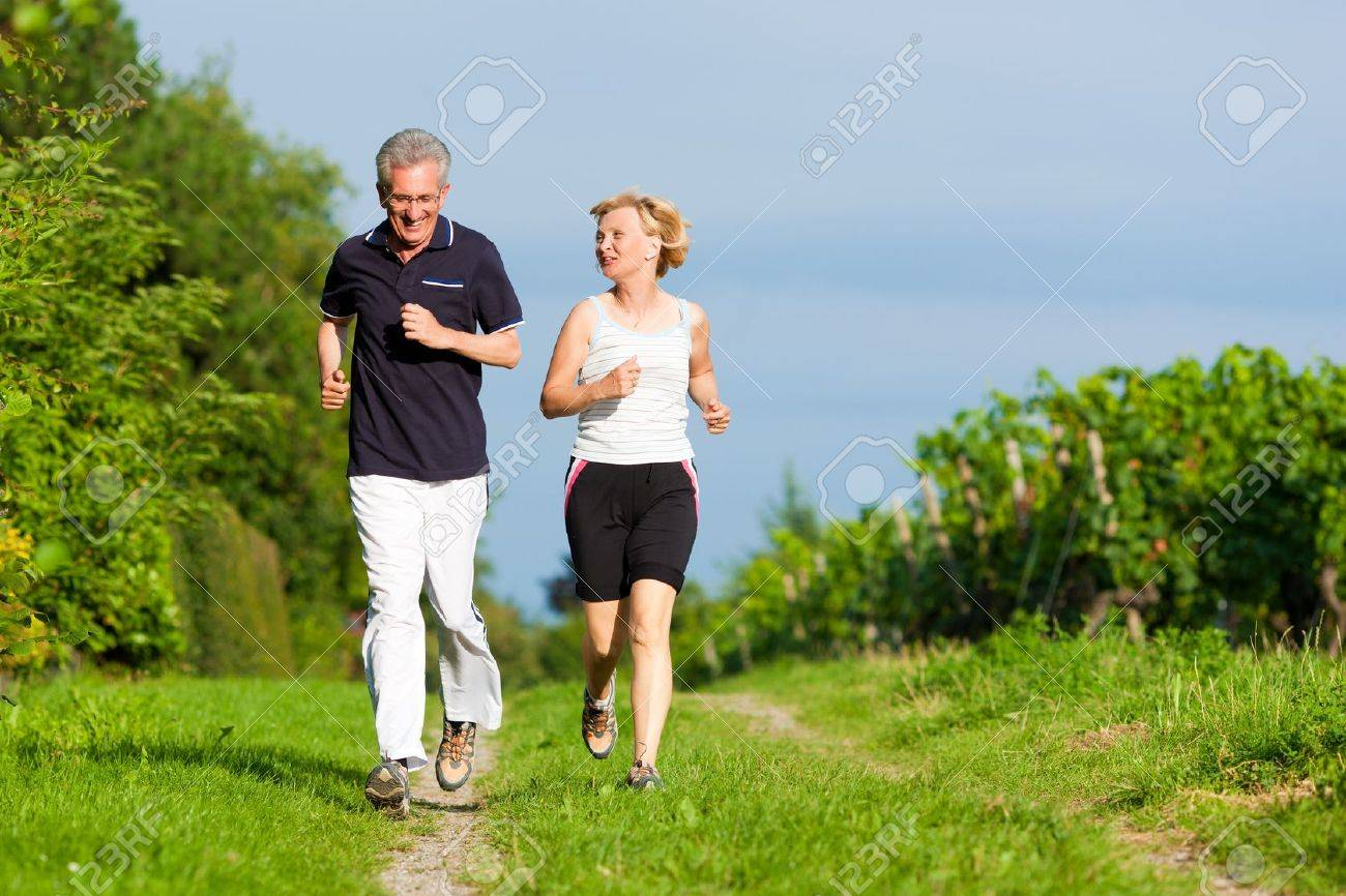 Mature or senior couple doing sport outdoors, jogging down a path in summer Stock Photo - 10769992