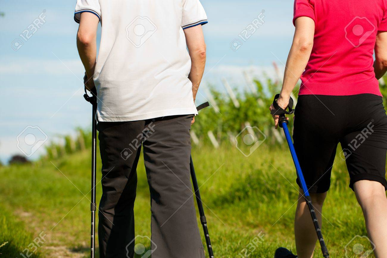 Nordic Walking - Happy mature or senior couple doing sports in summer outdoors Stock Photo - 11529744