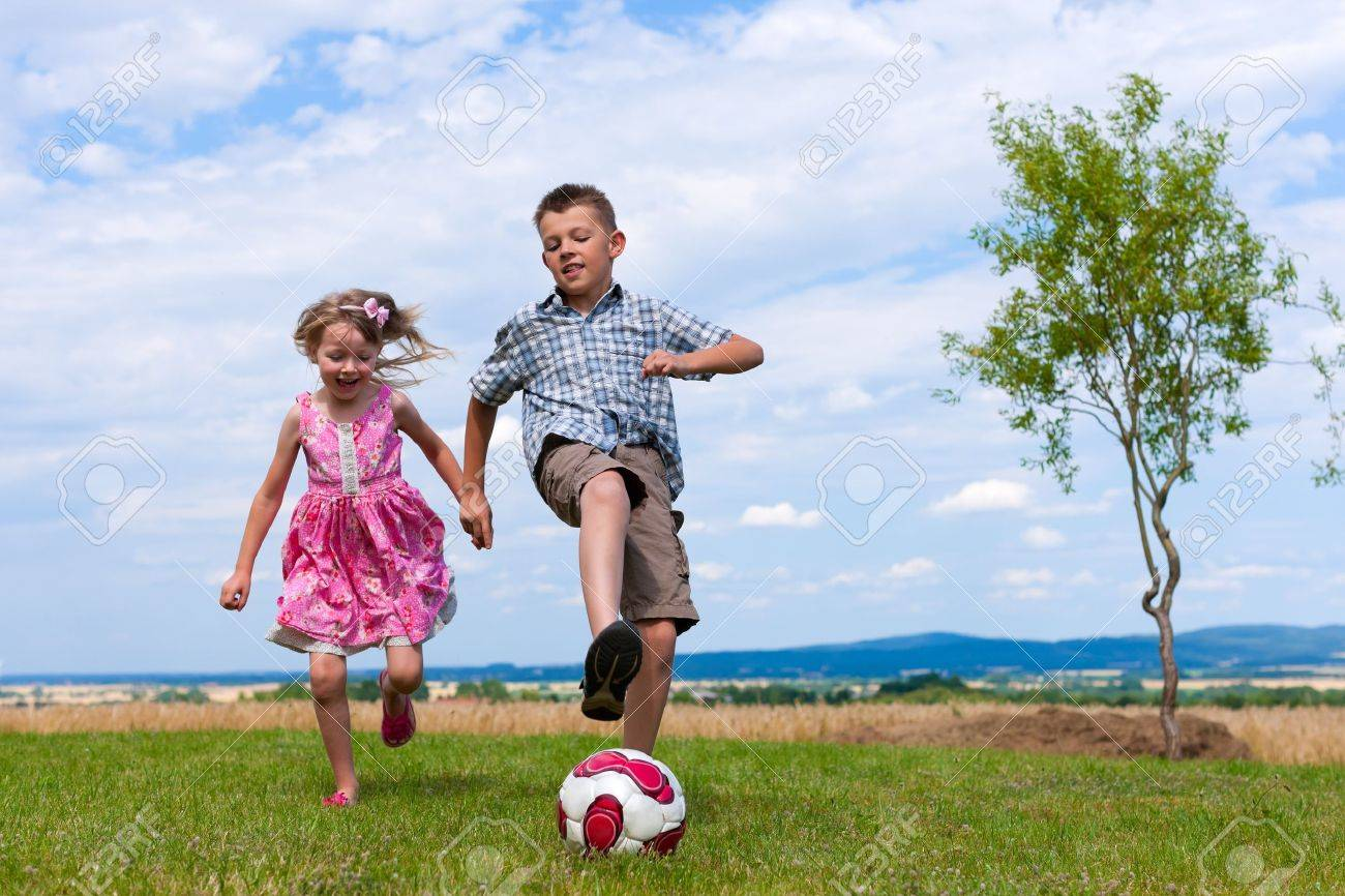 Siblings - son and daughter - playing soccer in the garden - 11529654