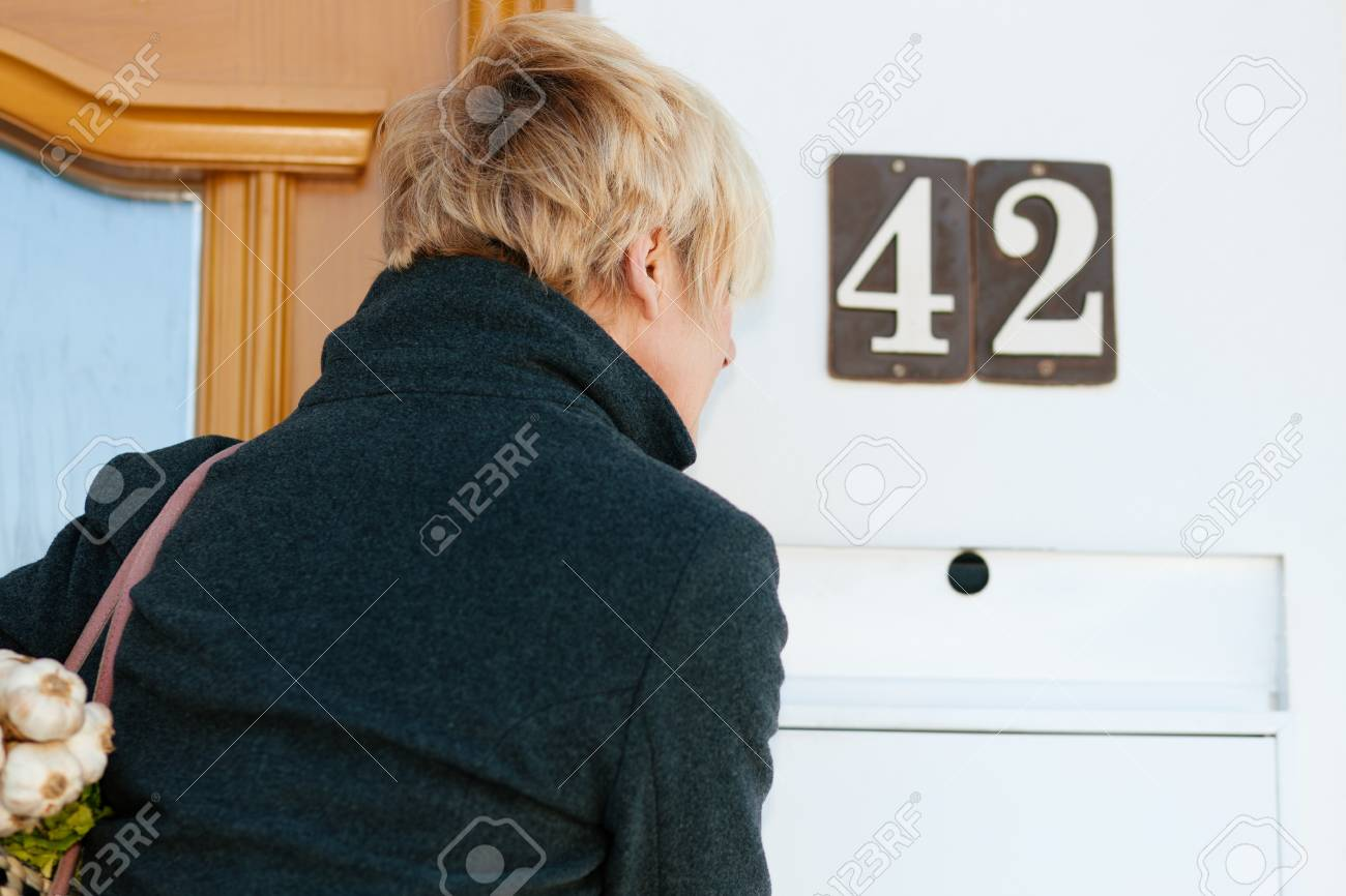 Woman with her groceries looking in her letter box Stock Photo - 11529983