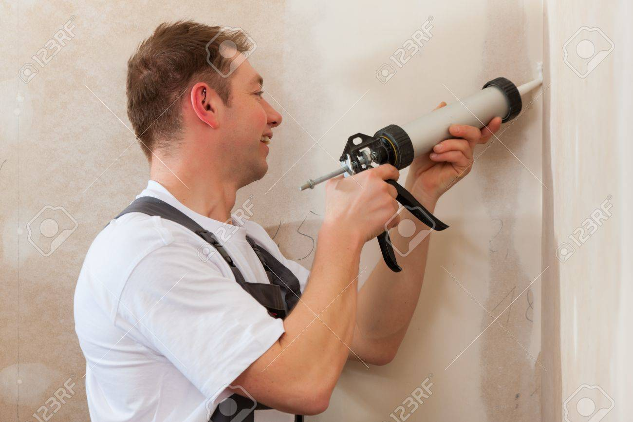 Worker grouts with silicone; it is presumably a new house Stock Photo - 11529996
