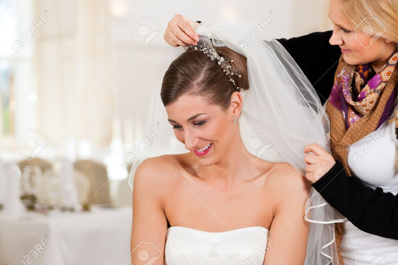 wedding planner stylist pinning up a brides hairstyle and bridal veil before the wedding stock