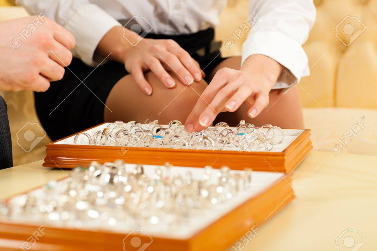 Couple choosing wedding rings at a jeweller Stock Photo - 11840840