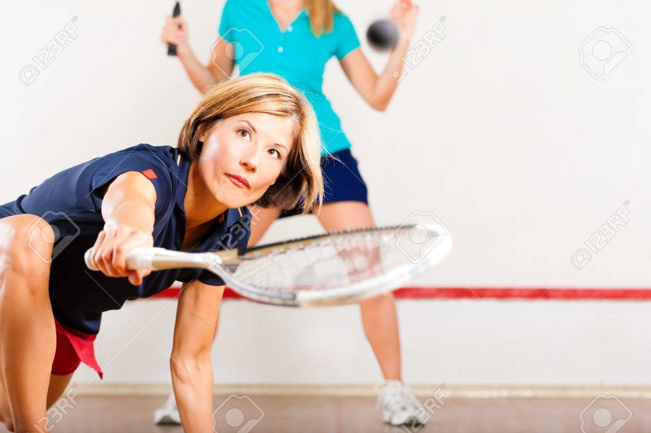 Two women playing squash as racket sport in gym, it might be a competition Stock Photo - 11840757