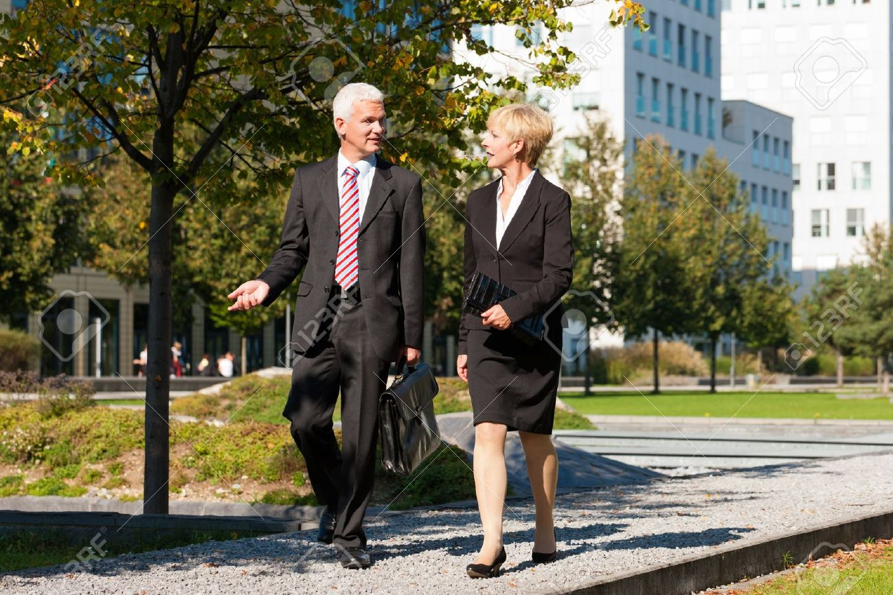 Business people - mature or senior -  talking outdoors and walking in a park Stock Photo - 11840632