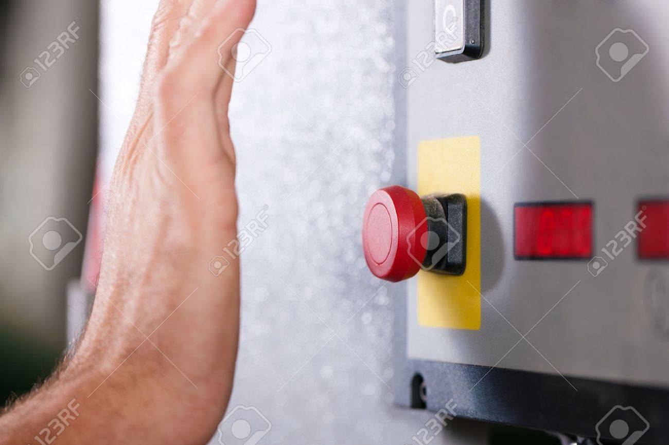 Man is shutting off a machine with the emergency button - probably in a case of danger Stock Photo - 11912058