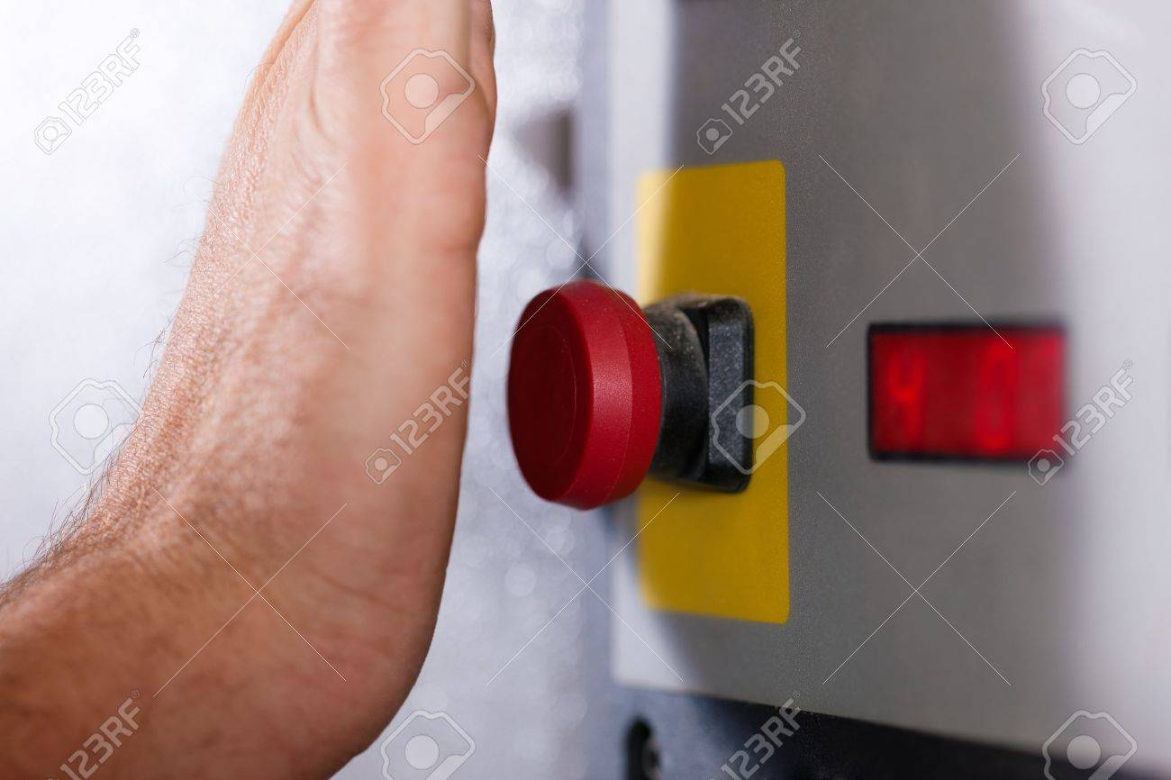 Man is shutting off a machine with the emergency button - probably in a case of danger Stock Photo - 11912021