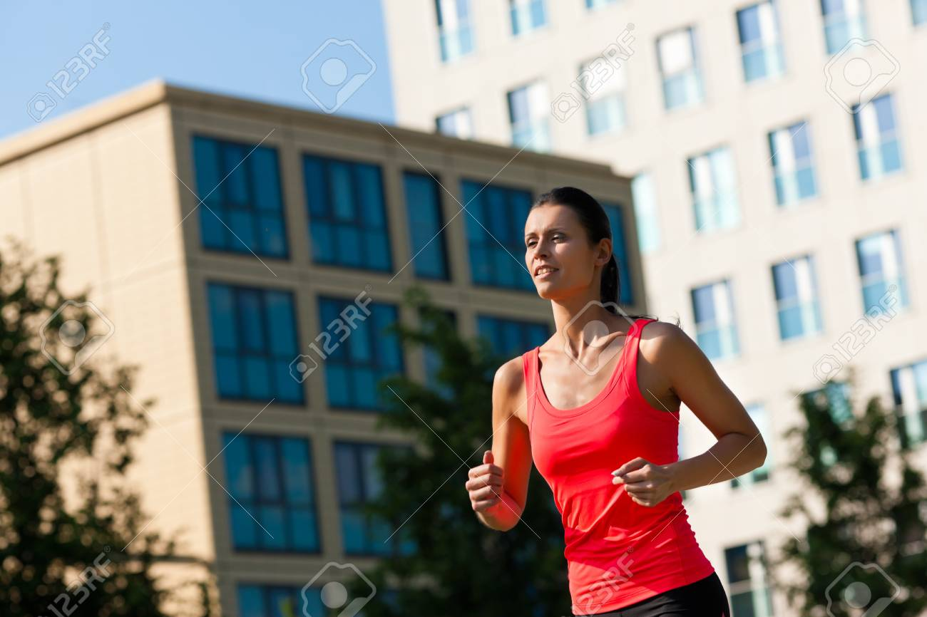 Urban sports - young woman jogging for fitness in the city on a beautiful summer day Stock Photo - 12443162