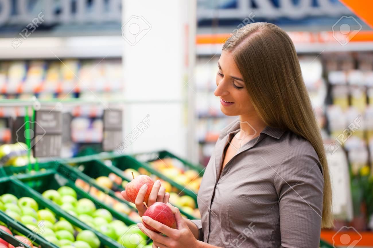 Beautiful female customer selecting apples at supermarket Stock Photo - 12388911