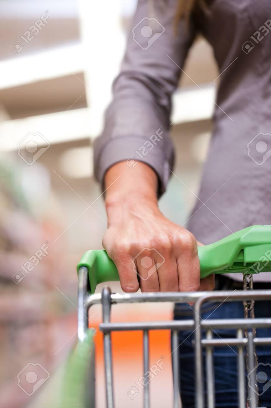 Cropped image of woman holding pushcart at supermarket Stock Photo - 12388918