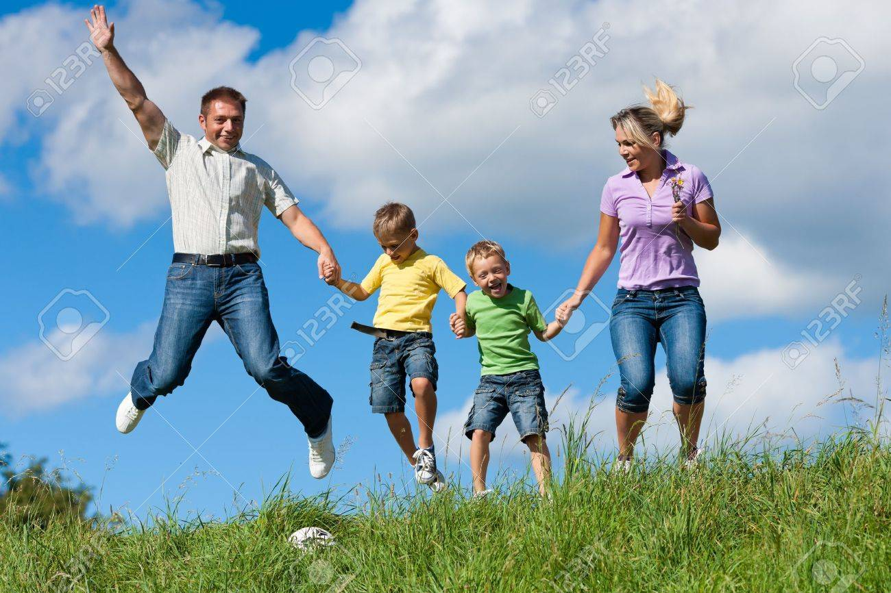 Happy family with children jumping in a meadow in summer - 12388922